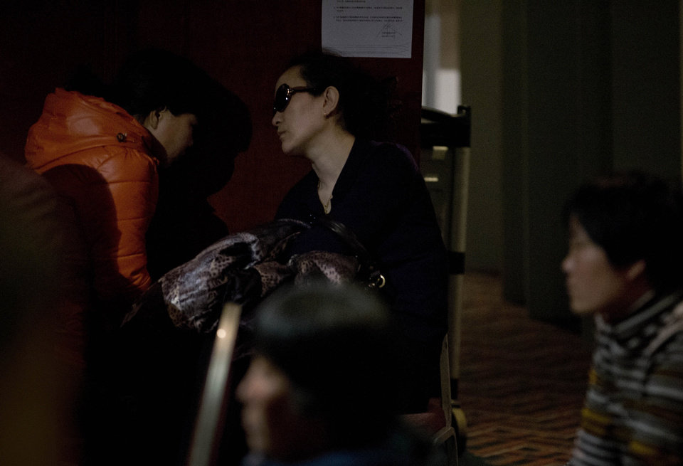 Photo - Relatives of Chinese passengers aboard the missing Malaysia Airlines, MH370 wait for news about the plane at a hotel ballroom in Beijing, China, Thursday, March 20, 2014. Four military search planes were dispatched Thursday to try to determine whether two large objects bobbing in a remote part of the Indian Ocean spotted by satellite imagery were part of a possible debris field of the missing Malaysia Airlines flight. (AP Photo/Andy Wong)