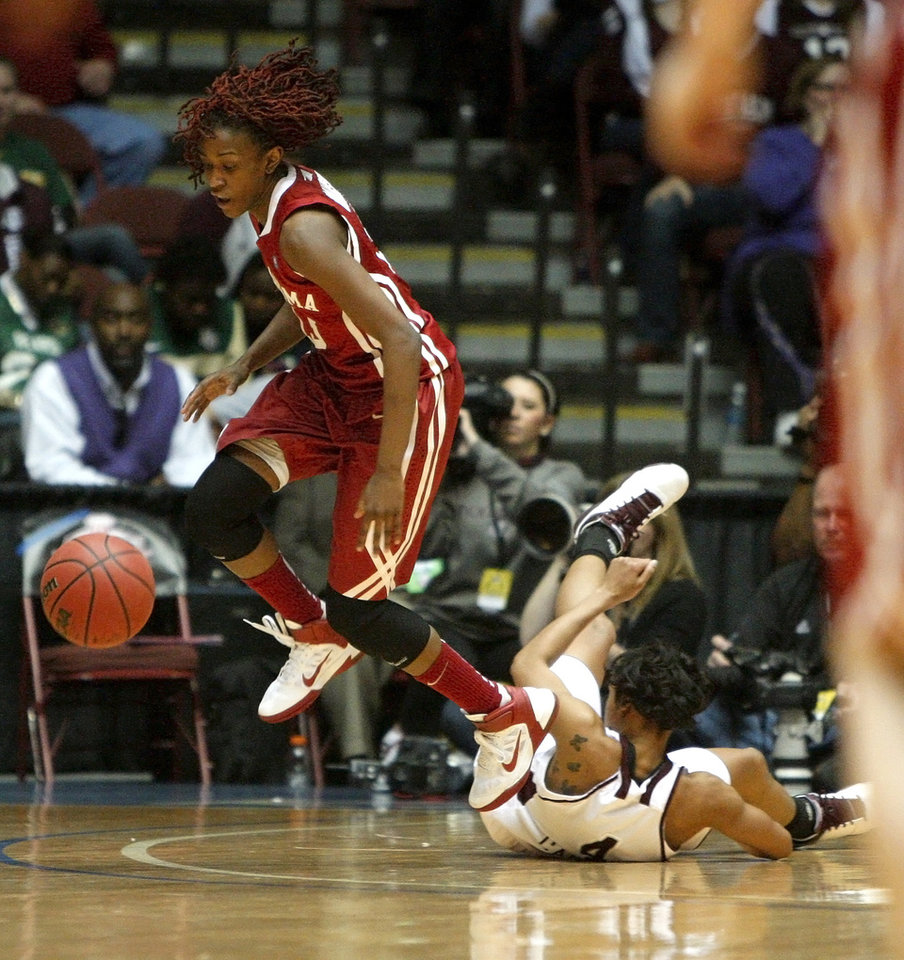 Photo - OU's Danielle Robinson (13) gains control of the ball over Texas A&M's Sydney Carter (4) during the women's college basketball Big 12 Championship tournament game between the University of Oklahoma and Texas A&M in Kansas City, Mo., Friday, March 11, 2011.  Photo by Bryan Terry, The Oklahoman