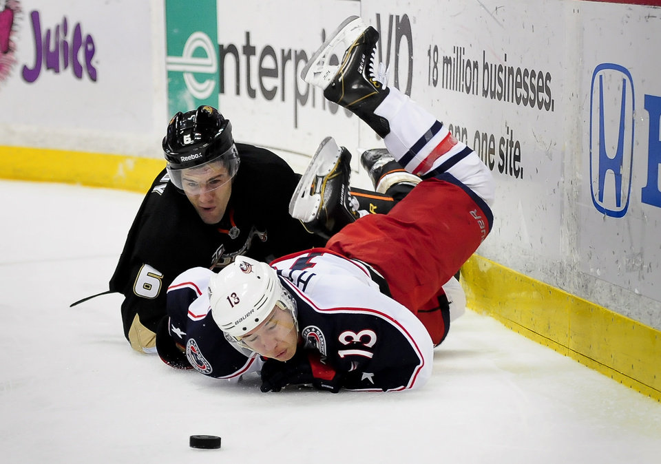 Photo - Anaheim Ducks defenseman Ben Lovejoy, left, and Columbus Blue Jackets right wing Cam Atkinson, battle for the puck during the first period of an NHL hockey game, Monday, Feb. 3, 2014, in Anaheim, Calif. (AP Photo/Gus Ruelas)