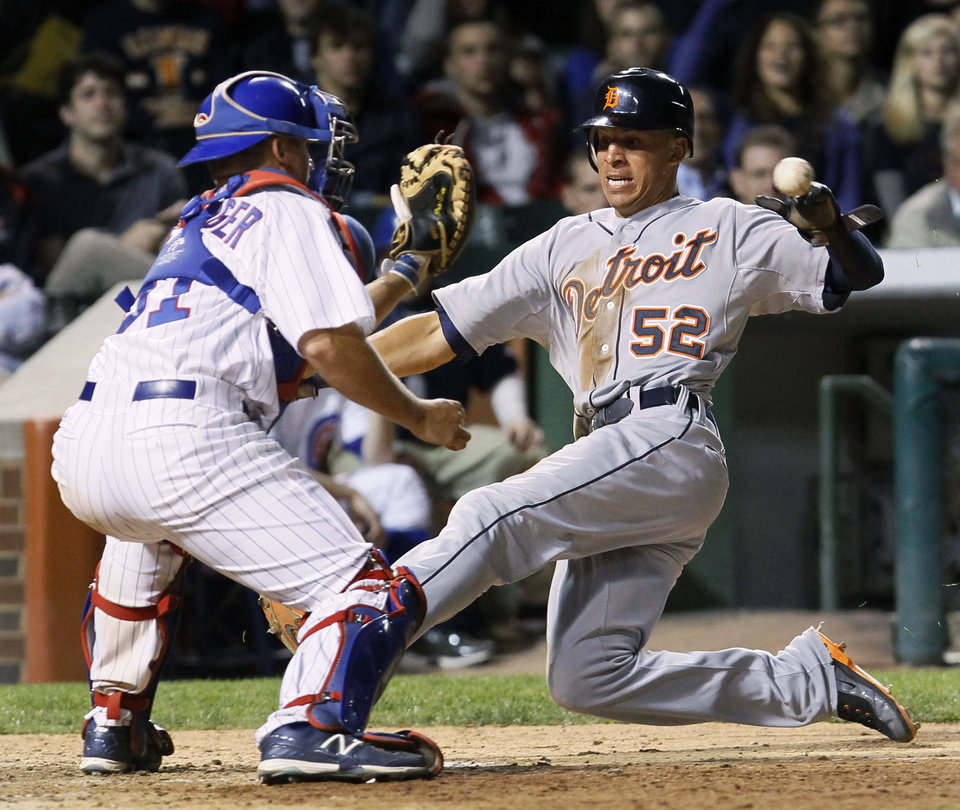 Photo -   Chicago Cubs catcher Steve Clevenger, left, takes a throw from left fielder Alfonso Soriano before tagging out Detroit Tigers' Quintin Berry during the eighth inning of an interleague baseball game Wednesday, June 13, 2012, in Chicago. Berry tried to score from second on a single by Brennan Boesch that scored Gerald Laird. (AP Photo/Charles Rex Arbogast)