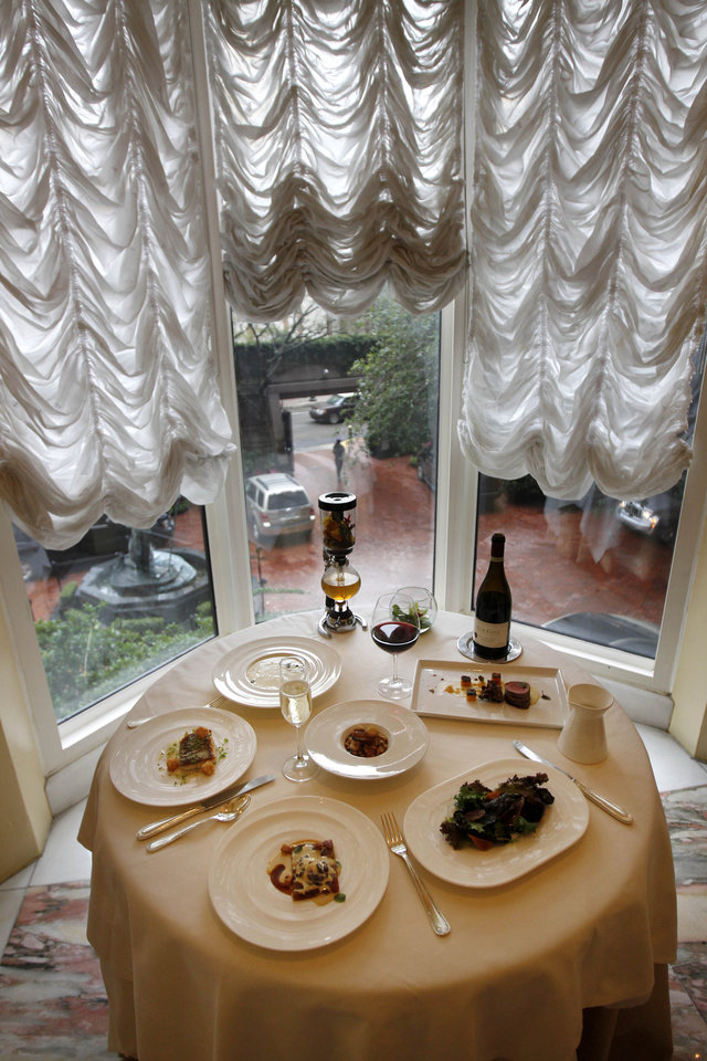 Photo - In this Dec. 7, 2012 photo, the reveillon menu of executive chef Kristin Butterworth, is seen with wine pairings and cafe brulot in a tea siphon, center rear, at the Grill Room of the Windsor Court Hotel on a rainy day in old New Orleans. Roughly 50 restaurants in New Orleans are reviving an old Creole custom called reveillon, which stems from the old French tradition of eating a lavish meal after midnight Mass on Christmas Eve. (AP Photo/Gerald Herbert)