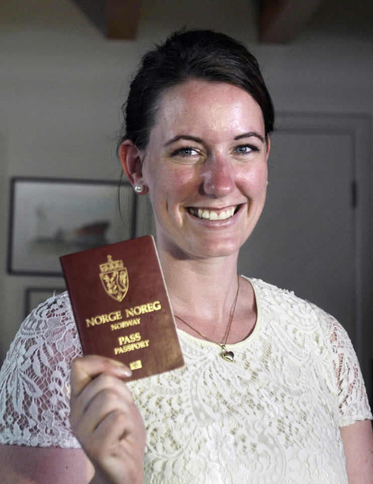 Photo - Norwegian Marte Deborah Dalelv, 24, shows her passport at the Norwegian Seaman's Club in Dubai, United Arab Emirates, Monday, July 22, 2013. Dalelv at the center of a Dubai rape claim dispute said Sunday that officials have dropped her 16-month sentence for having sex outside marriage and she is free to leave the country. (AP Photo/Kamran Jebreili)