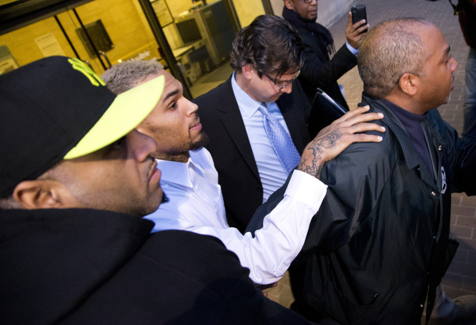 Photo - Singer Chris Brown is surrounded by bodyguards as he departs the H. Carl Moultriel courthouse Monday, Oct. 28, 2013, with one of his attorney's, Danny Onorato, center,, in Washington. A charge against the Grammy Award-winning R&B singer has been reduced to a misdemeanor and he was ordered released after his arrest Sunday following an altercation outside a Washington hotel. (AP Photo/ Evan Vucci)