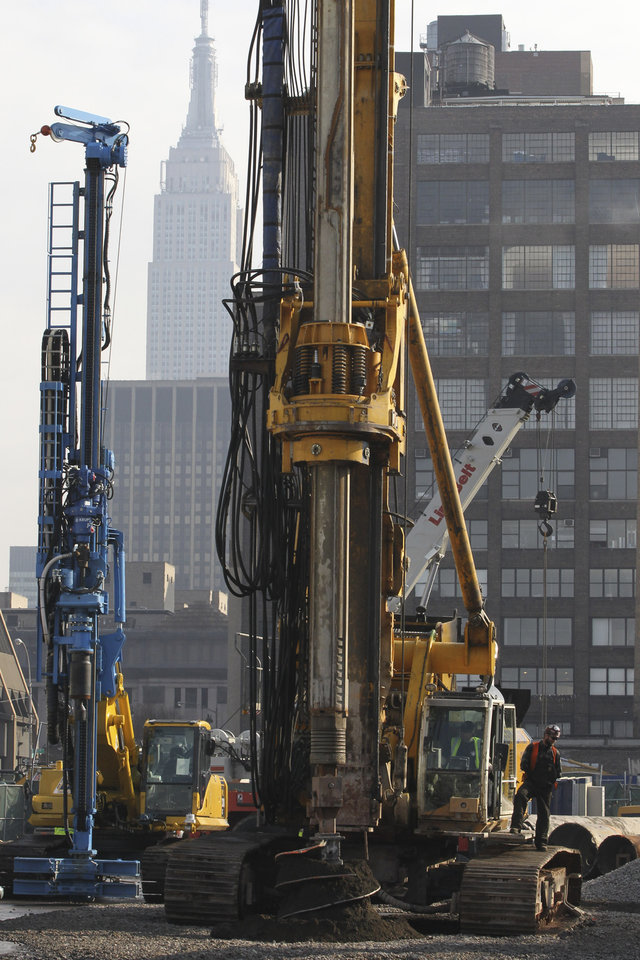 Photo - The Empire State building is seen in the background as a BG 40 drill rig breaks ground for a new neighborhood called Hudson Yards, Tuesday, Dec. 4, 2012 in New York.  The ambitious development is meant to transform the largest undeveloped property in Manhattan from an isolated rail yard into a sleek new neighborhood of spiky high-rises and graceful parks. (AP Photo/Mary Altaffer)
