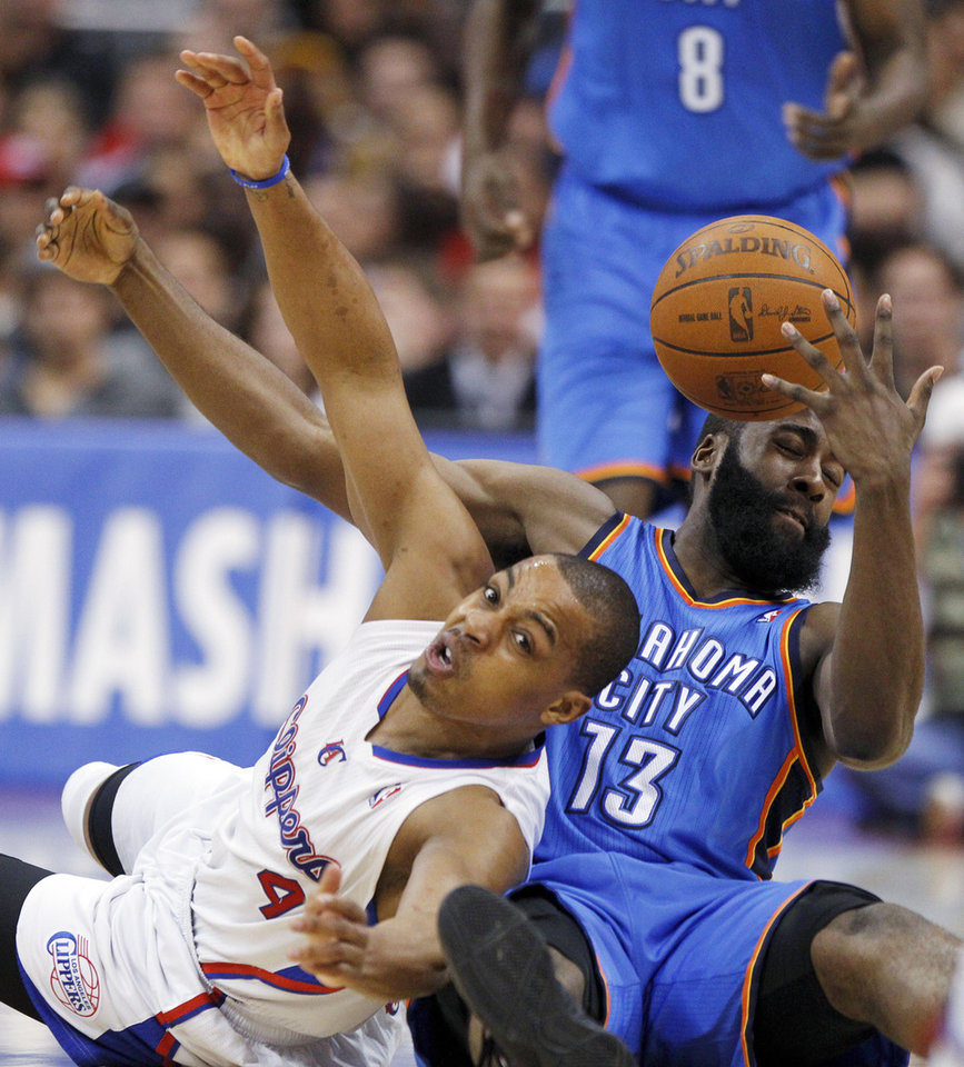 Photo - Oklahoma City guard James Harden, right, fights for a loose ball with Los Angeles Clippers guard Randy Foye during the first half of  Monday's game. AP PHOTO