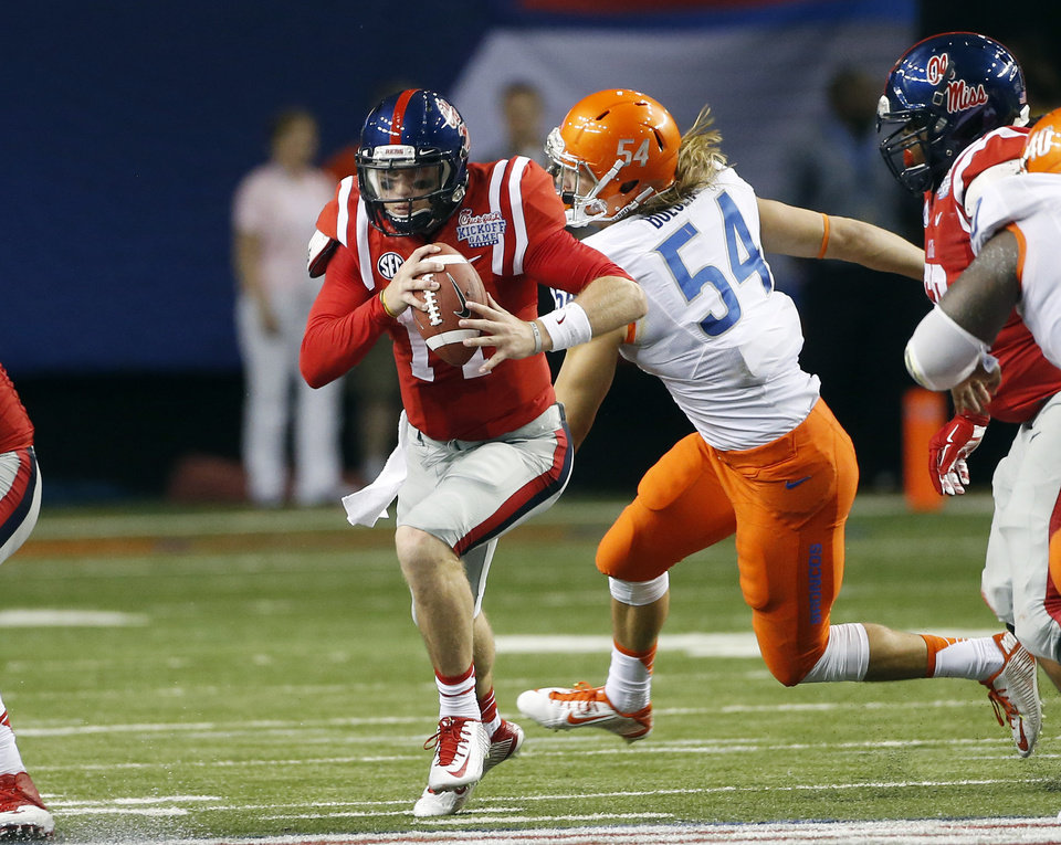 Photo - Mississippi quarterback Bo Wallace (14) runs past Boise State linebacker Mat Boesen (54) in the second half of an NCAA college football game, Thursday, Aug. 28, 2014, in Atlanta.  (AP Photo/John Bazemore)