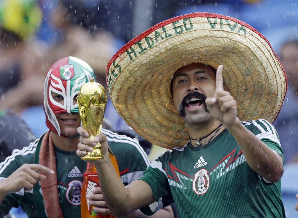 Photo - Mexican supporters gesure as they stand in  the rain before the start of the group A World Cup soccer match between Mexico and Cameroon in the Arena das Dunas in Natal, Brazil, Friday, June 13, 2014. (AP Photo/Ricardo Mazalan)
