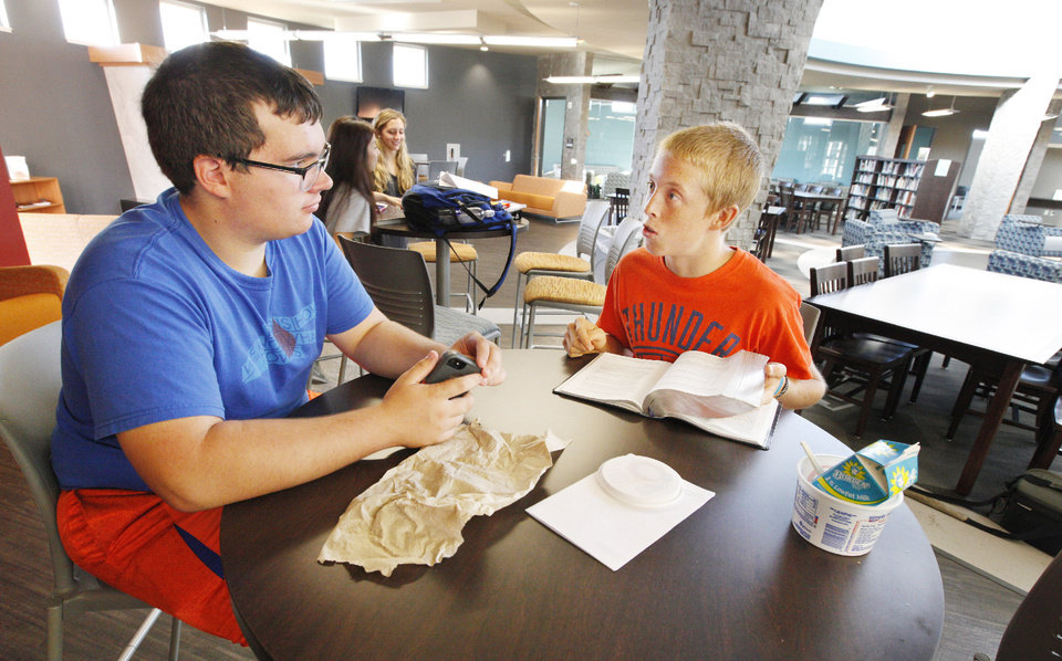 Photo - Seth Beam, 17, and Andrew Prescott, 18, use one of the tables in the new media center at Deer Creek High School.