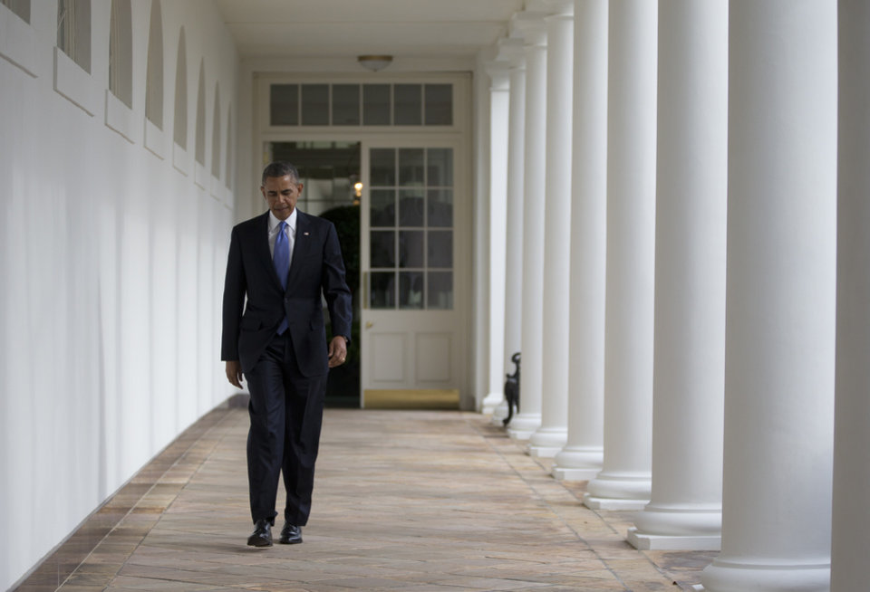 Photo - President Barack Obama walks along the Colonnade at the White House in Washington, Tuesday, Jan. 28, 2014, hours before giving his State of the Union Address before a joint session of Congress. (AP Photo/Carolyn Kaster)