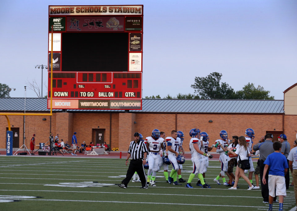 Photo - Power to the scoreboard, public address system and lights goes out in the second quarter stopping the game as Westmoore plays Moore High School on Friday, Sept. 6, 2013 in Moore, Okla.  Photo by Steve Sisney, The Oklahoman