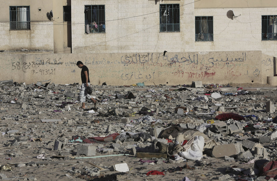 Photo - A Palestinian man walks on debris from a damaged building after it was hit by an Israeli airstrike in Beit Lahiya, northern Gaza Strip, Tuesday, July 15, 2014. The Israeli military says it has resumed airstrikes on Gaza after Hamas militants violated a de-escalation brokered by Egypt. (AP Photo/Adel Hana)