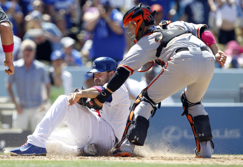 Photo - San Francisco Giants catcher Buster Posey, right, tags out Los Angeles Dodgers' Adrian Gonzalez trying to score from second base on a single  to center field in the sixth inning of a baseball game on Sunday, May 11, 2014, in Los Angeles. (AP Photo/Alex Gallardo)