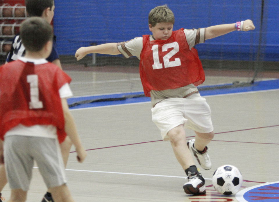 Alex Haworth, 11, shoots the ball during a soccer camp scrimmage.