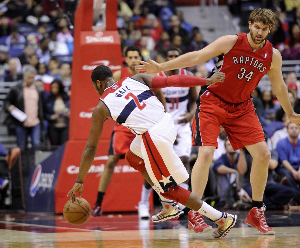 Photo - Washington Wizards guard John Wall (2) is fouled by Toronto Raptors center Aaron Gray (34) during the first half of an NBA basketball game, Sunday, March 31, 2013, in Washington. (AP Photo/Nick Wass)