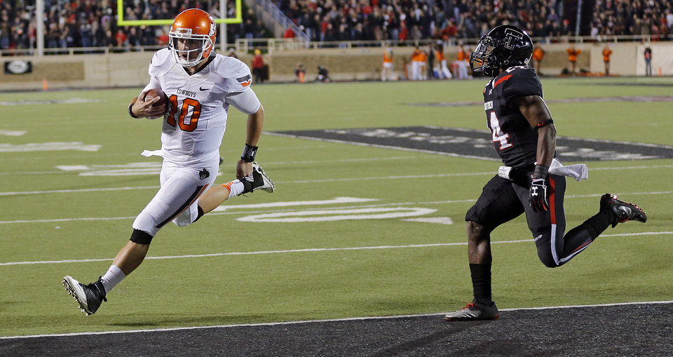Oklahoma State 's Clint Chelf (10) runs past Texas Tech's Bruce Jones (24) for a touchdown during the college football game between the Oklahoma State University Cowboys (OSU) and the Texas Tech University Red Raiders (TTU) at Jones AT&T Stadium in Lubbock, Tex. on Saturday, Nov. 2, 2013.  Photo by Chris Landsberger, The Oklahoman