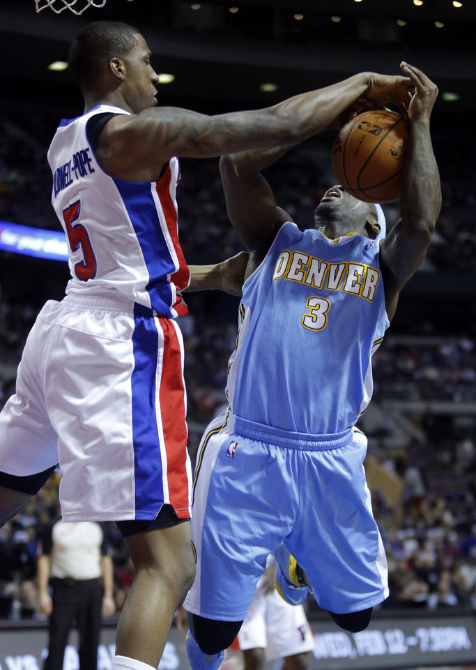 Photo - Detroit Pistons guard Kentavious Caldwell-Pope (5) blocks a shot by Denver Nuggets guard Ty Lawson (3) during the first half of an NBA basketball game on Saturday, Feb. 8, 2014, in Auburn Hills, Mich. (AP Photo/Duane Burleson)