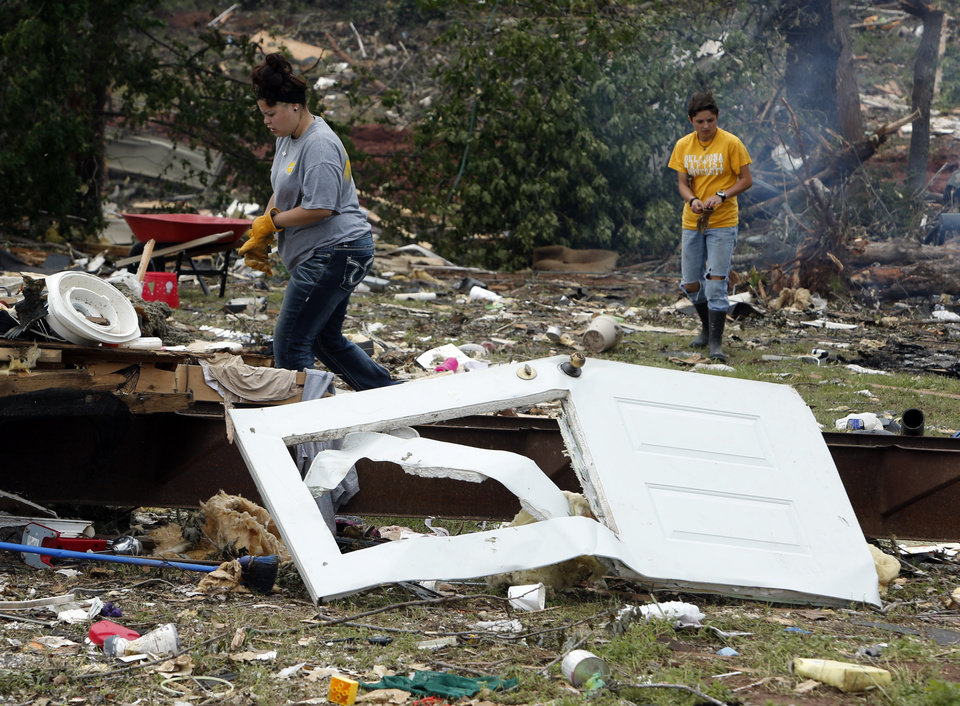 Oklahoma Baptist University students Patiance Villa and Alex Smith extend volunteer help to clean up damage from Sunday's tornado in the Woodlands and Pecan Valley area on Thursday, May 23, 2013 in Little Axe, Okla.  Photo by Steve Sisney, The Oklahoman