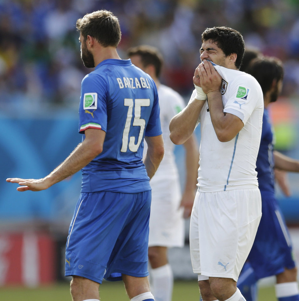 Photo - Uruguay's Luis Suarez, right, holds his teeth after running into Italy's Giorgio Chiellini's shoulder during the group D World Cup soccer match between Italy and Uruguay at the Arena das Dunas in Natal, Brazil, Tuesday, June 24, 2014. (AP Photo/Petr David Josek)