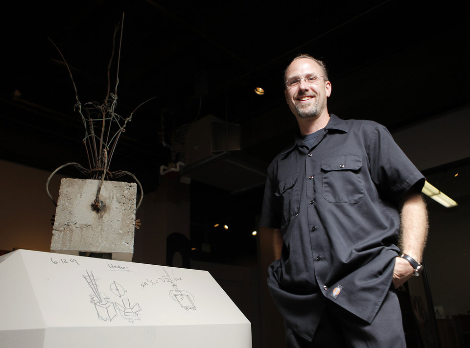 Eric Wright poses for a photo next to his art,