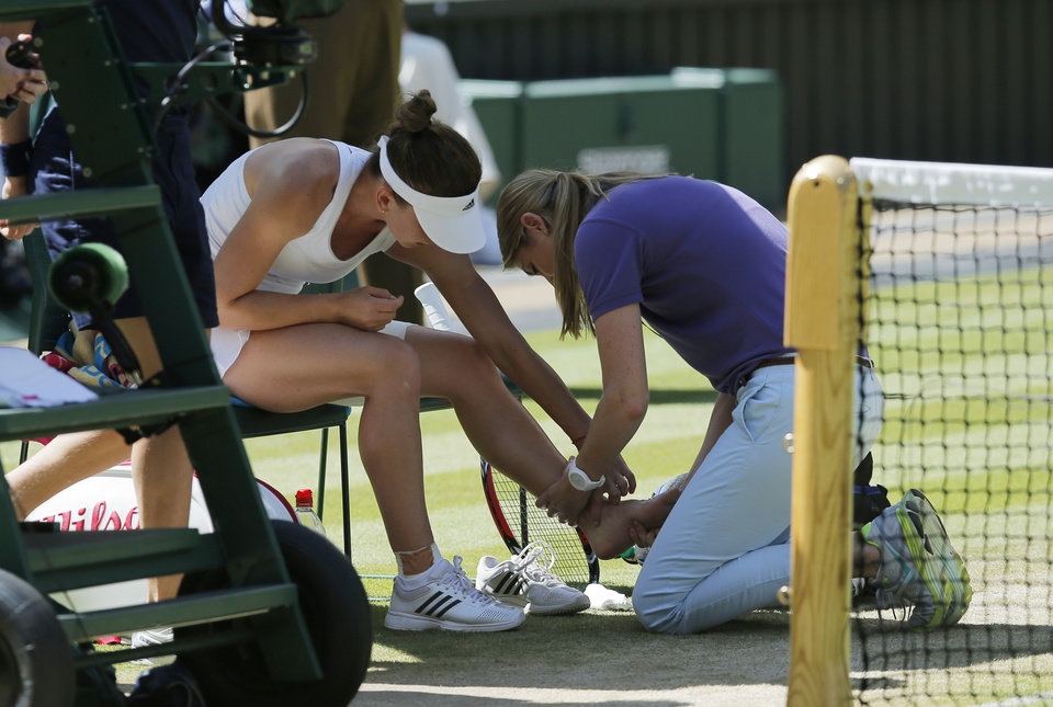 Photo - Simona Halep of Romania receives treatment on her ankle during the women's singles semifinal match against Eugenie Bouchard of Canada at the All England Lawn Tennis Championships in Wimbledon, London, Thursday, July 3, 2014. (AP Photo/Ben Curtis)