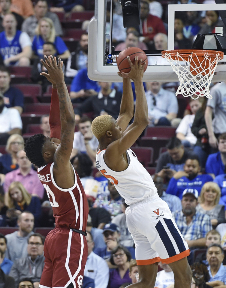 Photo - Virginia's Mamadi Diakite (25) pulls in a rebound while defended by Oklahoma's Kristian Doolittle (21) during the second half of a second-round men's college basketball game in the NCAA Tournament in Columbia, S.C. Sunday, March 24, 2019. (AP Photo/Richard Shiro)