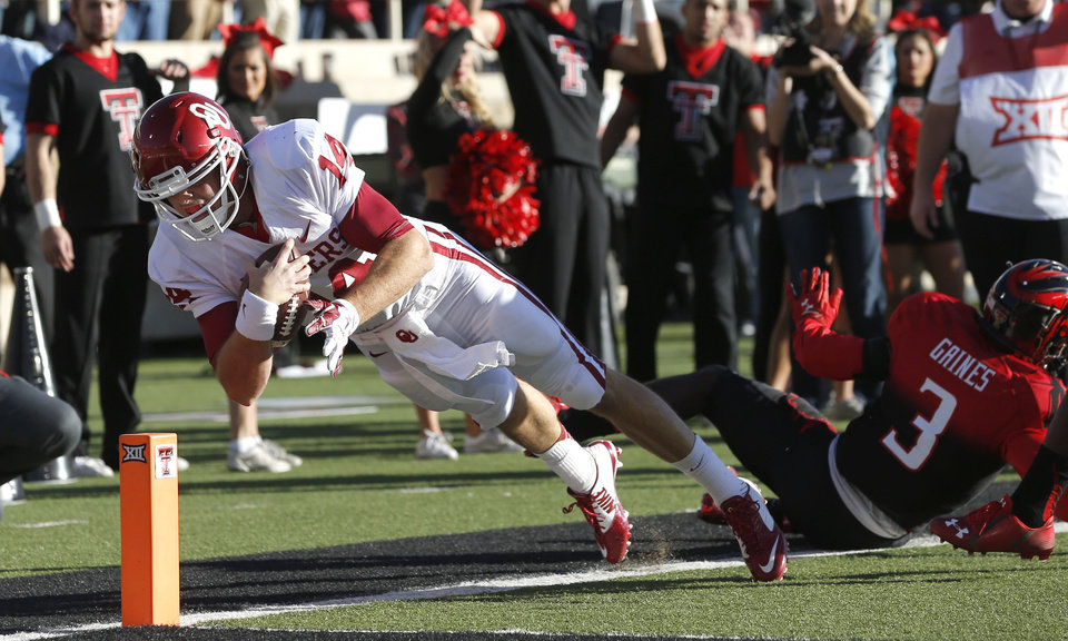 Photo - Oklahoma's Cody Thomas (14) comes up short of the end zone as he leaps past J.J. Gaines (3) during the college football game between the University of Oklahoma Sooners (OU) and the Texas Tech Red Raiders at Jones AT&T Stadium in Lubbock, Texas, Saturday, November 15, 2014.  Photo by Bryan Terry, The Oklahoman