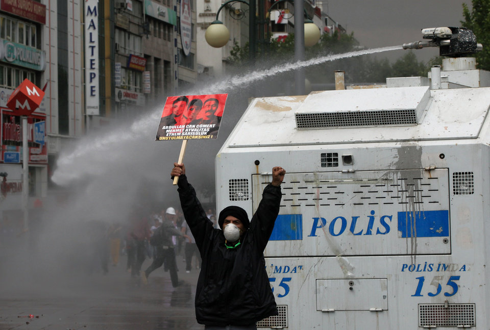 Photo - A protester holds up a banner with photos of three victims killed during protests and shouts anti-government slogans as Turkish riot police spray water cannon at demonstrators who remained defiant after authorities evicted activists from an Istanbul park, making clear they are taking a hardline against attempts to rekindle protests that have shaken the country, in city's main Kizilay Square in Ankara, Turkey, Sunday, June 16, 2013.(AP Photo/Burhan Ozbilici)