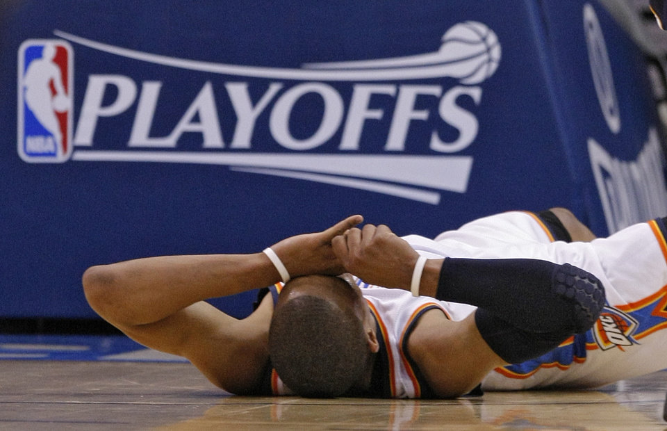 Photo - Oklahoma City's Russell Westbrook reacts after being knocked to the court during game one of the Western Conference semifinals between the Memphis Grizzlies and the Oklahoma City Thunder in the NBA basketball playoffs at Oklahoma City Arena in Oklahoma City, Sunday, May 1, 2011. Photo by Chris Landsberger, The Oklahoman