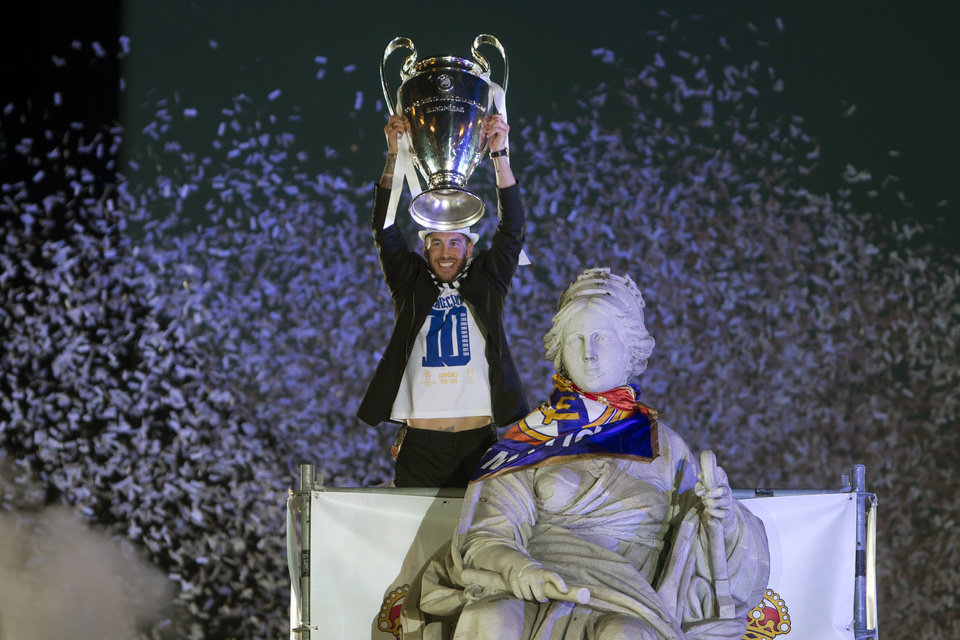 Photo - Real Madrid's Sergio Ramos lifts the trophy next to the Cibeles statue in Madrid, Spain, Sunday, May 25, 2014, after the team won the Champions League final soccer match in Lisbon by beating Atletico Madrid. (AP Photo/Paul White)
