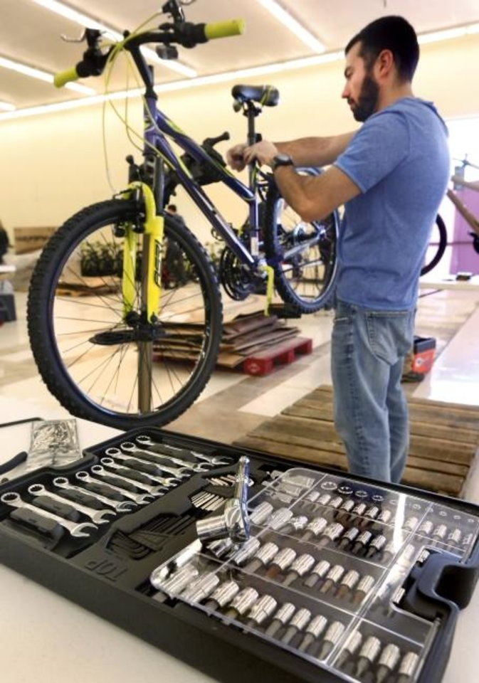 Photo -  Ilya Golberg, of Oklahoma City, assembles a bicycle during the 2018