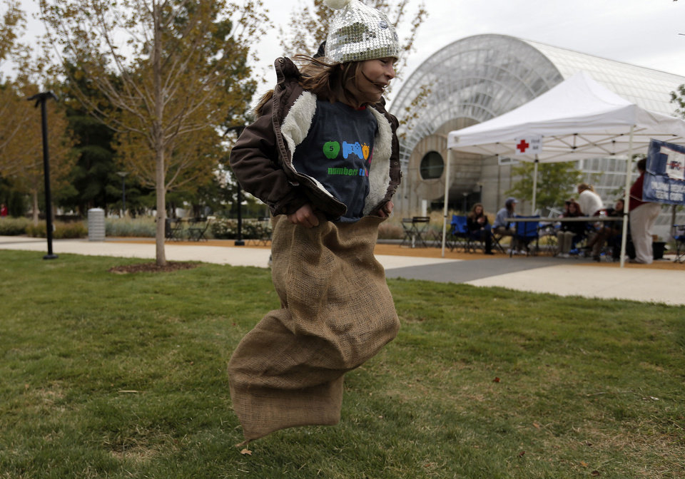 Define Mansour jumps in a potato sack during the YMCA 5210 event at Myriad Gardens in Oklahoma City. Photo by Sarah Phipps, The Oklahoman <strong>SARAH PHIPPS - SARAH PHIPPS</strong>
