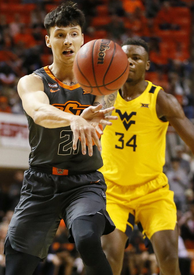Photo - Oklahoma State's Lindy Waters III (21) passes in front of West Virginia's Oscar Tshiebwe (34) in the first half during a men's college basketball game between the Oklahoma State Cowboys and West Virginia Mountaineers at Gallagher-Iba Arena in Stillwater, Okla., Monday, Jan. 6, 2020. [Nate Billings/The Oklahoman]