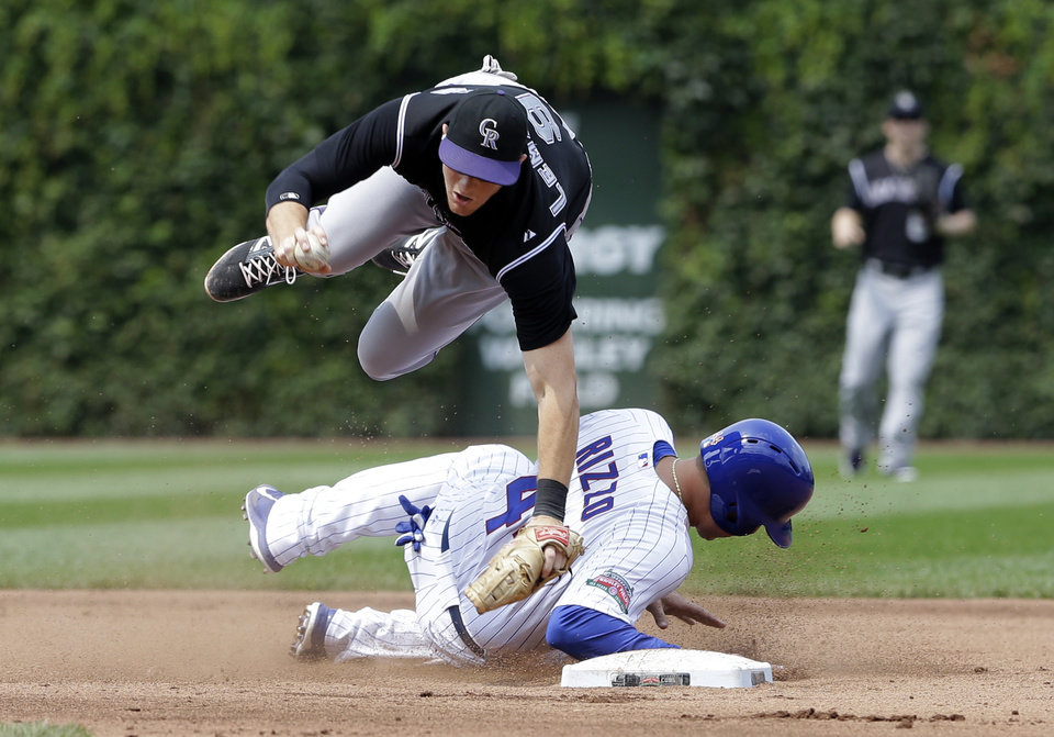 Photo - Colorado Rockies second baseman D.J. LeMahieu, top,  jumps over Chicago Cubs'  Anthony Rizzo after forcing him out at second base during the fourth inning of a baseball game in Chicago, Thursday, July 31, 2014. Starlin Castro was safe at first base on the play. (AP Photo/Nam Y. Huh)