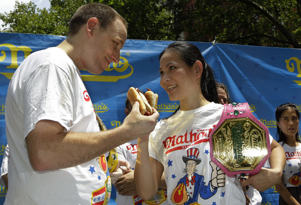 FILE - In this Tuesday, July 3, 2012 file photo, five-time hot-dog eating world champion Joey Chestnut, left, and women's record-holder Sonya Thomas, center, face each other during a weigh-in for contestants in the annual Coney Island Fourth of July international hot-dog eating contest in New York. The two are due to defend their respective men's and women's titles in the 2013 competition. (AP Photo/Kathy Willens)