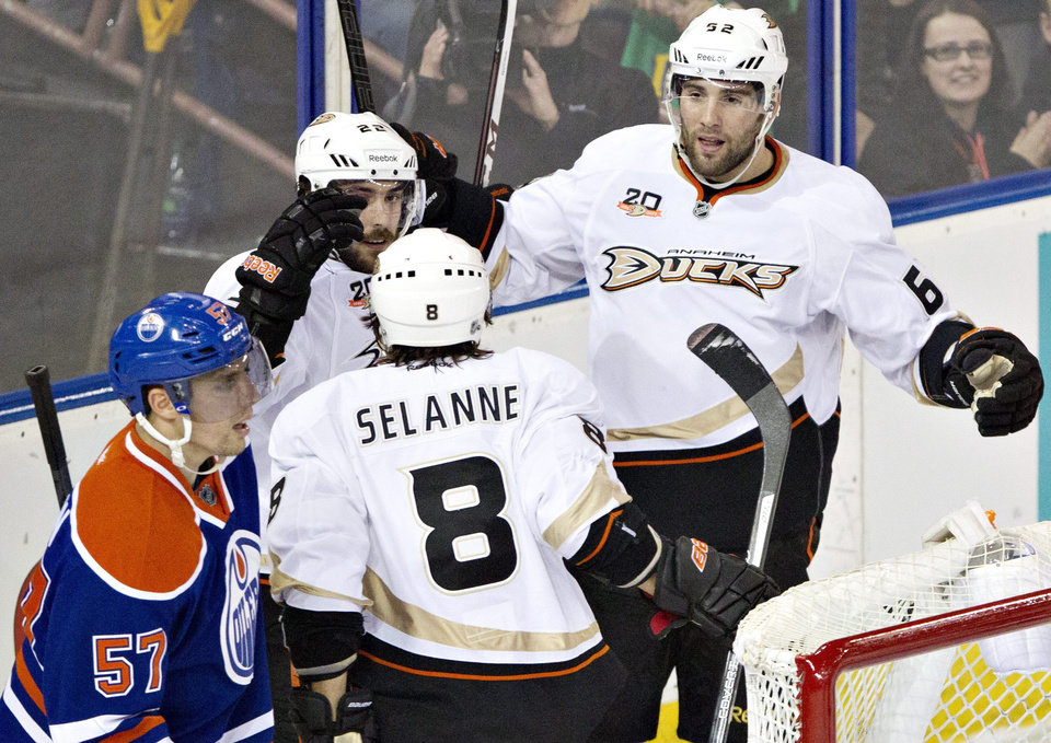Photo - Anaheim Ducks' Mathieu Perreault (22), Teemu Selanne (8) and Patrick Maroon (62) celebrate a goal as Edmonton Oilers' David Perron (57) skates past during second-period NHL hockey game action in Edmonton, Alberta, Friday, March 28, 2014. (AP Photo/The Canadian Press, Jason Franson)