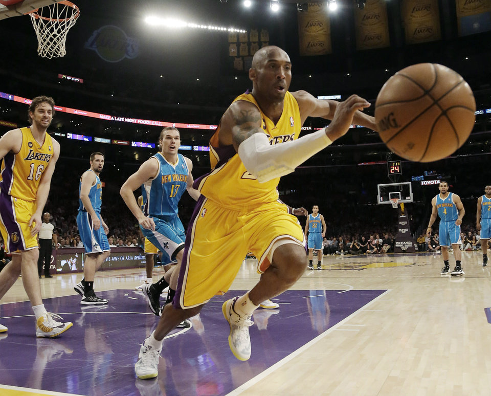 Photo - Los Angeles Lakers guard Kobe Bryant (24) chases a loose ball against the New Orleans Hornets in the first half of an NBA basketball game in Los Angeles Tuesday, April 9, 2013.  (AP Photo/Reed Saxon)