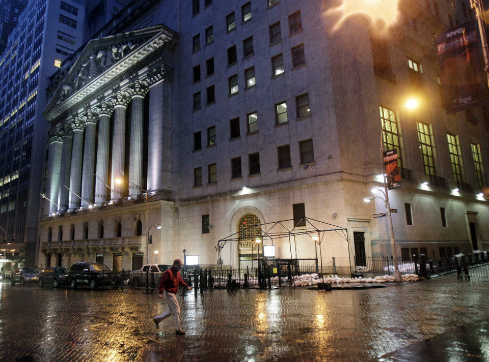 A man crosses the street in front of the New York Stock Exchange, Monday, Oct. 29, 2012. Hurricane Sandy continued on its path Monday, forcing the shutdown of mass transit, schools and financial markets, sending coastal residents fleeing, and threatening a dangerous mix of high winds and soaking rain. There had been plans to allow electronic trading to go forward on the New York Stock Exchange but with a storm surge expected to cover parts of lower Manhattan in water, officials decided late Sunday that it was too risky to ask any personnel to staff the exchanges. (AP Photo/Richard Drew) ORG XMIT: NYRD102