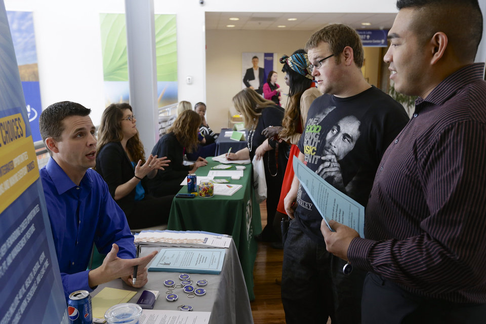 Photo - In this April 10, 2014 photo, John Soung, right, and Gabriel Fitzgerald, second right, talk to recruiter Todd Zedicher of Integrated Life Choices, left, at a job fair on the campus of Kaplan University in Lincoln, Neb. The Labor Department on Friday, May 2, 2014 said U.S. employers added a robust 288,000 jobs in April, the most in two years, the strongest evidence to date that the economy is picking up after a brutal winter slowed growth.  (AP Photo/Nati Harnik)