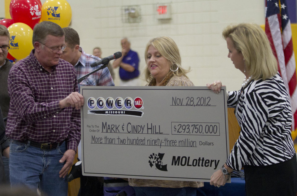 Photo - Mark, left, and Cindy, center, Hill are presented a check by a Missouri Lottery official during the announcement of Powerball winners in Dearborn, Mo., Friday, Nov. 30, 2012. (AP Photo/Orlin Wagner)