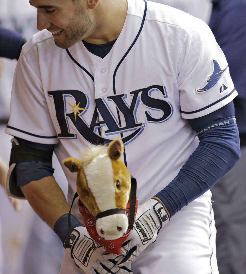 Photo - Tampa Bay Rays' Kevin Kiermaier rides a child's pony in the dugout after hitting a home run off Miami Marlins starting pitcher Jacob Turner during the fifth inning of an interleague baseball game Thursday, June 5, 2014, in St. Petersburg, Fla. (AP Photo/Chris O'Meara)