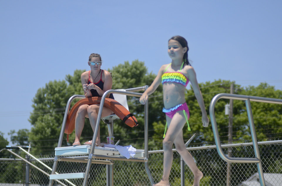Photo - Darci Thomas, 20, watches as a child prepares to go off the diving board at the Stillwater Municipal Pool. PHOTO ADAM KEMP, THE OKLAHOMAN  Adam Kemp