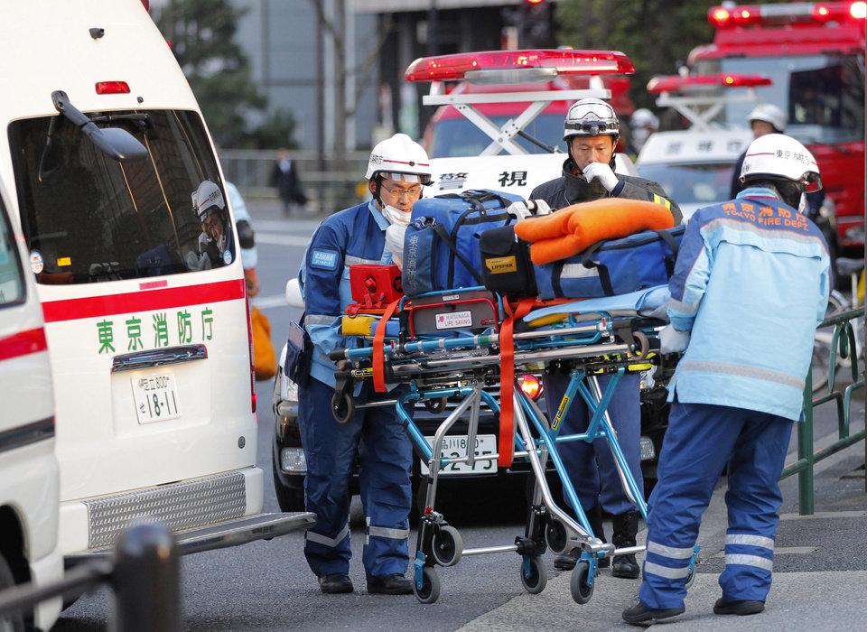 Photo - Tokyo Fire Department rescue workers arrive at Kudan Kaikan in Tokyo as local media said its ceiling was damaged after a strong earthquake and injured people inside the hall Friday, March 11, 2011. (AP Photo/Itsuo Inouye) ORG XMIT: XITS105