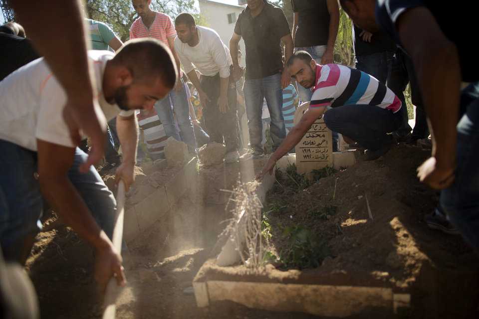 Photo - Friends and relatives of Mohammed Krakra, an Israeli Arab teen, gather around the grave site during his funeral at the northern Israeli Arab village of Arabeh, Israel, Monday, June 23, 2014. Israeli warplanes bombed the Syrian military headquarters and a number of other targets inside Syria, the Israeli military said Monday, in a blistering response to a cross-border attack that killed Krakra the previous day. (AP Photo/Oded Balilty)