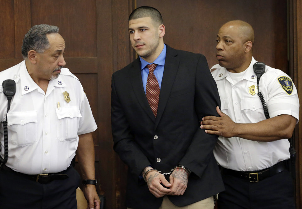 Photo - Former New England Patriots football player AaronHernandez, center, is escorted by court officers as he enters Suffolk Superior Court before a hearing, Tuesday, June 24, 2014, in Boston. Prosecutors allege that Hernandez ambushed and shot to death two men, Daniel de Abreu and Safiro Furtado, in 2012 after a chance encounter inside a Boston nightclub. Hernandez has pleaded not guilty. (AP Photo/Steven Senne, Pool)