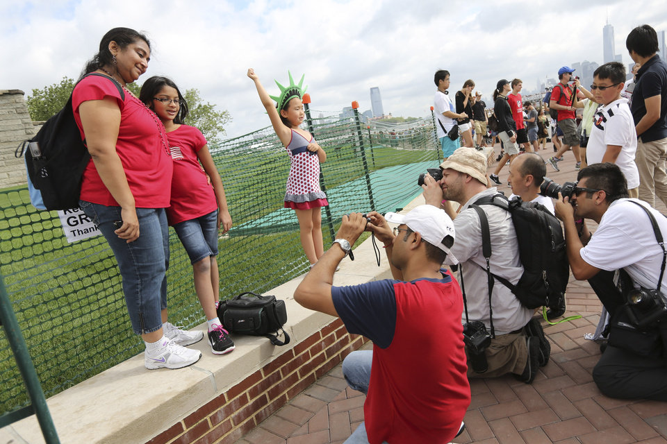 Photo - Photographers take photos of people posing for pictures a the base of the Statue of Liberty, Thursday, July 4, 2013 at  in New York. The Statue of Liberty finally reopened on the Fourth of July months after Superstorm Sandy swamped Liberty Island in New York Harbor as Americans across the country marked the holiday with fireworks and barbecues. (AP Photo/Mary Altaffer)