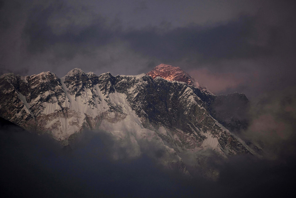 Photo - FILE - In this Oct. 27, 2011 file photo, the last light of the day sets on Mount Everest as it rises behind Mount Nuptse as seen from Tengboche, in the Himalaya's Khumbu region, Nepal. An avalanche swept the slopes of Mount Everest on Friday, April 18, 2014, along a route used to ascend the world's highest peak, killing at least six Nepalese guides and leaving nine more missing, officials said. (AP Photo/Kevin Frayer, File)