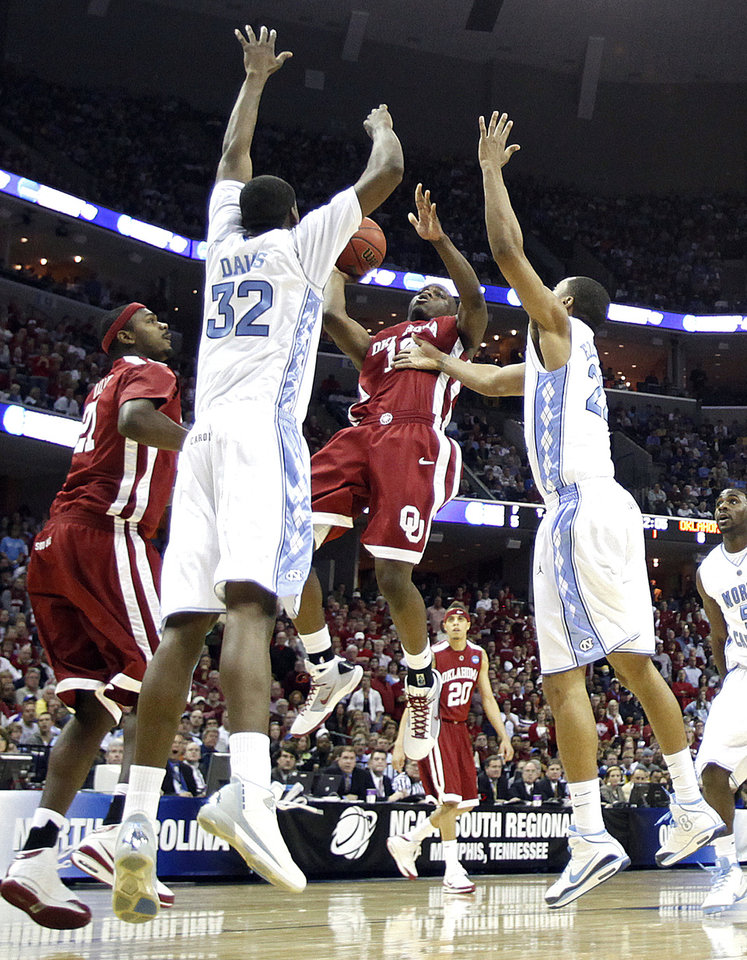Photo - Oklahoma's Willie Warren (13) tries to get off a shot through North Carolina's Ed Davis (32) and Wayne Ellington (22) during the first half in the Elite Eight game of NCAA Men's Basketball Regional between the University of North Carolina and the University of Oklahoma at the FedEx Forum on Sunday, March 29, 2009, in Memphis, Tenn.