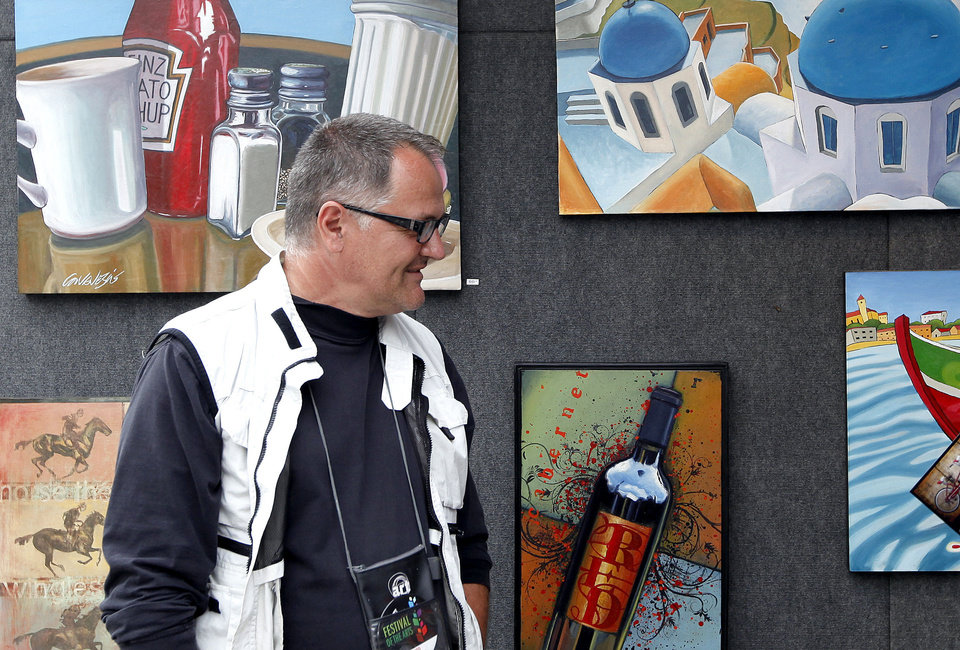 Photo - David Canavesio talks with people at his booth Sunday during the Festival of the Arts in Oklahoma City. Photos by Sarah Phipps, The Oklahoman