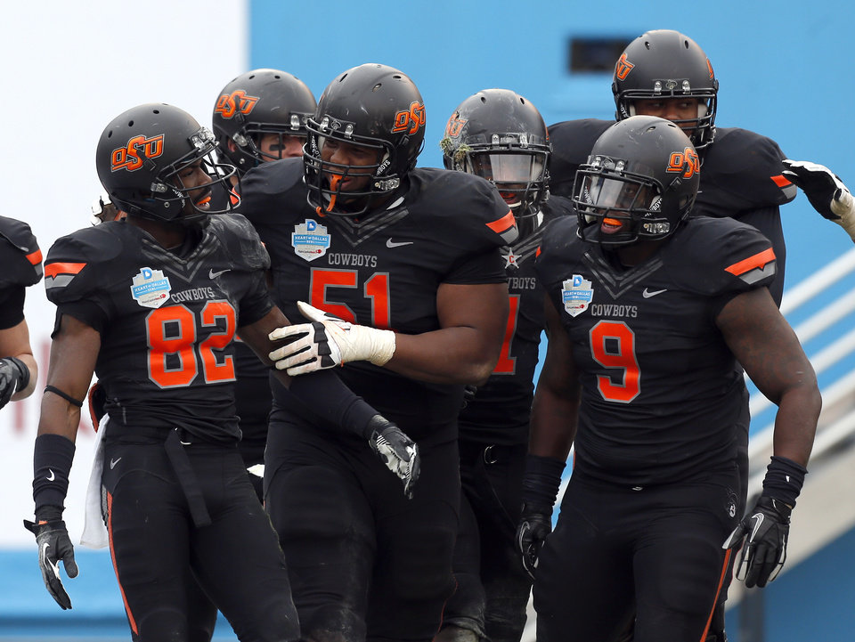 Photo - OSU celebrates a Isaiah Anderson (82) touchdown during the Heart of Dallas Bowl football game between the Oklahoma State University (OSU) and Purdue University at the Cotton Bowl in Dallas,  Tuesday,Jan. 1, 2013. Photo by Sarah Phipps, The Oklahoman