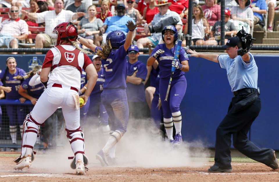 Photo - Washington's Julia DePonte (4) reacts as Trysten Melhart (2) is called safe at home next to Oklahoma's Lea Wodach (15) in the top of the fifth inning during the second game of the Women's College World Series between the Oklahoma Sooners (OU) and Washington Huskies at USA Softball Hall of Fame Stadium in Oklahoma City, Thursday, May 31, 2018. Washington won 2-0. Photo by Nate Billings, The Oklahoman